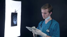 Male doctor at work in medical clinic examining x-ray plates of head. stock footage
