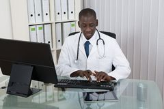 Male Doctor Working On Computer. Young Happy African Doctor Working On Computer At Desk Royalty Free Stock Photography