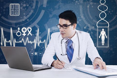 Male doctor working at the desk Royalty Free Stock Photos