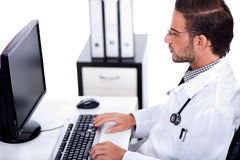 Male doctor working with desktop at his desk Royalty Free Stock Photography