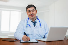 A male doctor works in a medical center. Look into the camera and smile. Good mood Stock Photography