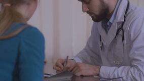 Male Doctor Writes a Prescription to His Young Female Patient and Gives it to Her with Some Oral Recommendations. stock video