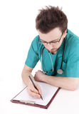 Male doctor writing on clipboard Stock Photos