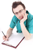 Male doctor writing on clipboard Royalty Free Stock Image