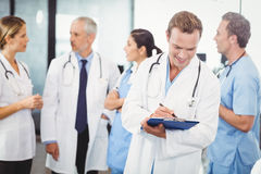 Male doctor writing on clipboard. And colleagues standing behind and discussing in hospital Stock Image