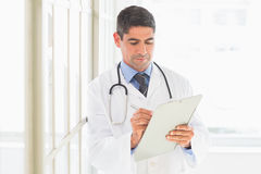 Male doctor writing on clipboard. In hospital Stock Photo