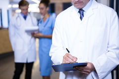 Male doctor writing on clipboard. In hospital Royalty Free Stock Photos