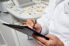 Male Doctor Writing On Clipboard. Midsection of male doctor writing on clipboard with ultrasonic machine in background Stock Photo