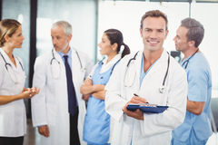Male doctor writing on clipboard. Portrait of male doctor writing on clipboard and colleagues standing behind and discussing in hospital Royalty Free Stock Photo