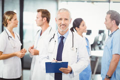 Male doctor writing on clipboard. Portrait of male doctor writing on clipboard and colleagues standing behind and discussing in hospital Stock Image