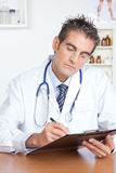 Male Doctor Writing on Clipboard Royalty Free Stock Images