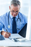 Male doctor writing data in file at hospital. Male doctor writing on file while sitting at desk in hospital Royalty Free Stock Photography