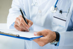 Male Doctor Writing On Medical Document. Close-up Of Male Doctor Filling The Medical Form