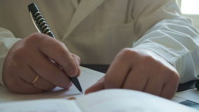 Male doctor writing medical history pan. Male doctor writing medical history at the table pan, close stock footage