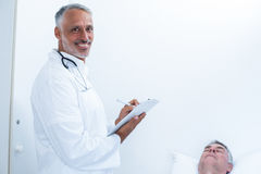 Male doctor writing medical report of senior man on clipboard. Happy male doctor writing medical report of senior men on clipboard in the hospital Stock Image