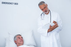 Male doctor writing medical report of senior man on clipboard. Male doctor writing medical report of senior men on clipboard in hospital Stock Image