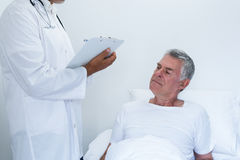 Male doctor writing medical report of senior man on clipboard. Male doctor writing medical report of senior men on clipboard in the hospital Stock Photography