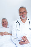 Male doctor writing medical report of senior man on clipboard. Male doctor writing medical report of senior men on clipboard in hospital Stock Photography
