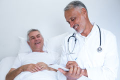 Male doctor writing medical report of senior man on clipboard. Male doctor writing medical report of senior men on clipboard in hospital Stock Photo