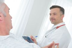 Male doctor writing medical report senior man on clipboard royalty free stock photography