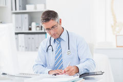 Male doctor writing on paper at table Royalty Free Stock Photos