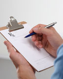 Male doctor writing prescription on clipboard Royalty Free Stock Images