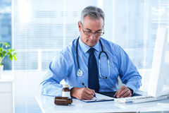 Male doctor writing prescription in hospital. Male doctor writing prescription white sitting at desk in hospital Stock Photography
