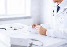 Male doctor writing prescription paper. Close up of male doctor writing prescription paper Stock Photo