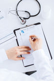 Male doctor writing prescription paper. Close up of male doctor writing prescription paper Royalty Free Stock Photo