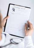 Male doctor writing prescription paper. Close up of male doctor writing prescription paper Royalty Free Stock Photography