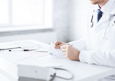 Male doctor writing prescription paper. Close up of male doctor writing prescription paper Stock Image