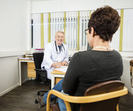 Male Doctor Writing Prescription For Patient At Desk. In clinic Royalty Free Stock Photos