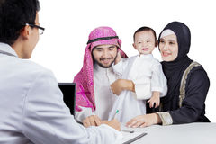 Male doctor writing a prescription on studio. Image of male doctor writing a prescription for Arab family, isolated on white background Stock Images