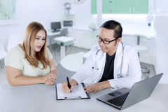Male doctor writing a prescription to his patient. Young male doctor writing a prescription to his patient after checkup while sitting in the clinic Royalty Free Stock Photography