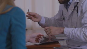 Male doctor writing rx prescription for female patient stock video footage