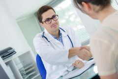 Male doctor and young smiling patient in office royalty free stock photos