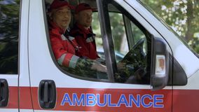 Male doctors in ambulance looking at camera, professional emergency service royalty free stock images