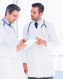 Male doctors using digital tablet in medical office Stock Photography