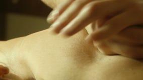 Male doing massage on back in spa salon. Close shot massage specialist massaging woman s back at beauty salon stock video footage