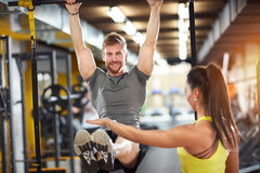 Male doing pull-up exercise with coach assisting. In fitness club Stock Photos
