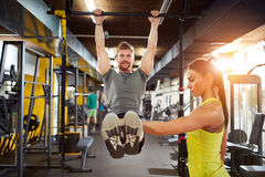 Male doing pull-up exercise with coach assisting Stock Photo