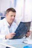 Male doktor som i regeringsställning ser röntgenstrålebild Arkivfoto