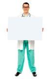Male doktor som visar det vita annonserande brädet Royaltyfri Fotografi