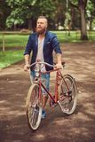 Male dressed in casual clothes, walking with a retro bicycle in a city park. Male dressed in casual clothes, walking with a retro bicycle in a park stock photos