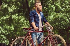Male dressed in casual clothes, walking with a retro bicycle in a city park. Male dressed in casual clothes, walking with a retro bicycle in a park royalty free stock image