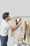 Male dressmaker adjusting suit on tailor's dummy in design studio Stock Photos