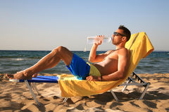 Male drinking water. Handsome male drinking water at the beach Royalty Free Stock Image