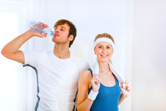 Male drinking water and girl in sportswear Stock Photos