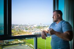 Male drinks coffee and looks through  panoramic window smiles in the morning royalty free stock photo