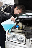 Male driver fills antifreeze liquid in washer window Stock Photography